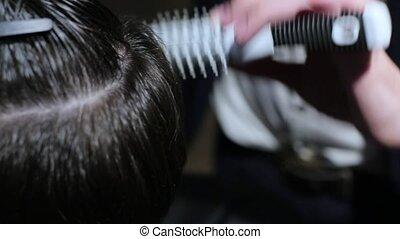 Man combing hair at the barbershop close up