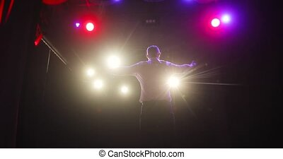 Man comedian clapping hands with audience on stage after sucsessful performance.