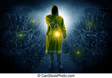 Man coming out from a thicket with lantern - Man in raincoat...