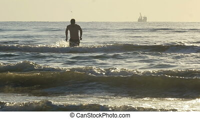 Man coming out from the sea after swimming