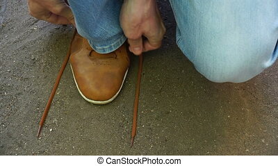 man commits an outdoor walk and stopped to tie his shoelaces...
