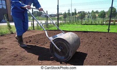 Man Compacts Soil With Hand Metal Roller. Gimbal movement...
