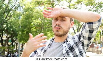 Man complaining suffering a heat stroke on summer -...