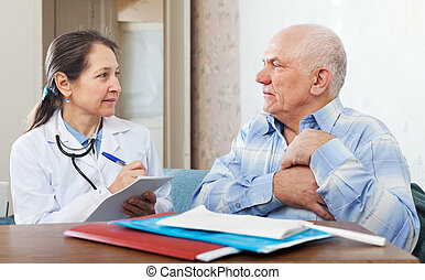 man complaining to doctor about heartache - Mature man...