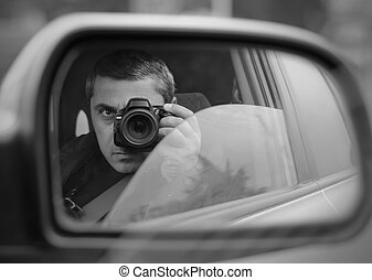 man conducts the hidden photographing with the car