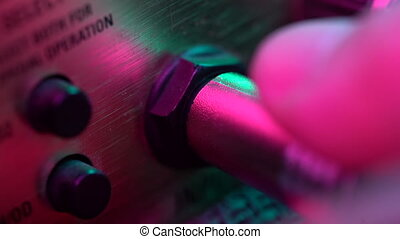 Man connects the jack to the amp. Colorful neon light. Close up view. Concert, music concept