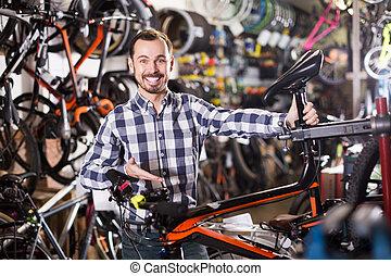 Man considers bicycle saddle