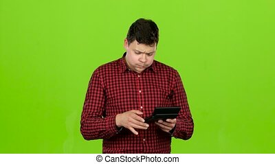 Man considers the profit on the calculator and he is bankrupt. Green screen