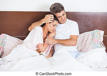 Man consoles his wife, couple bed in bedroom
