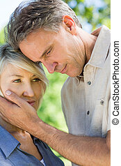 Man consoling woman in park