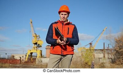 man construction worker in an orange helmet holding documents background blue sky and crane