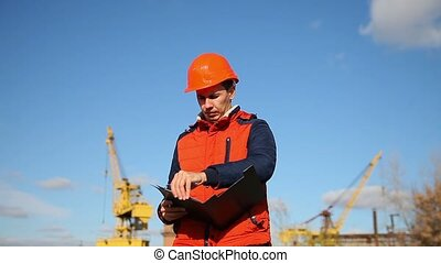 man construction worker in an orange helmet holding documents in background blue sky and a crane