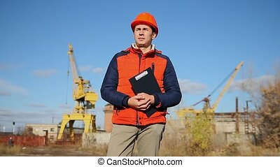 man construction worker in an orange helmet holding documents in background blue sky and crane