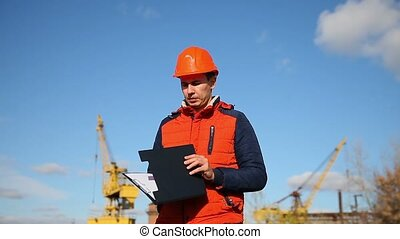 man construction worker in an orange helmet holding documents in the background blue sky and a crane