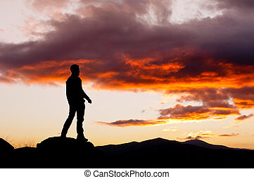 Man s silhouette in the high of a hill in a spectacular sunset