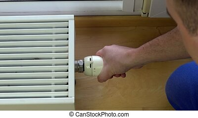 Man control climate at home. - adjustment of thermostat of...