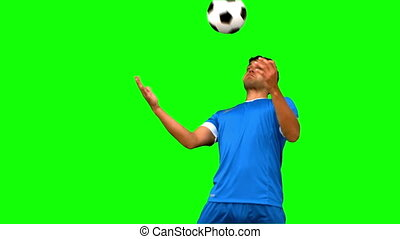 Man controlling a football with his chest on green screen in...