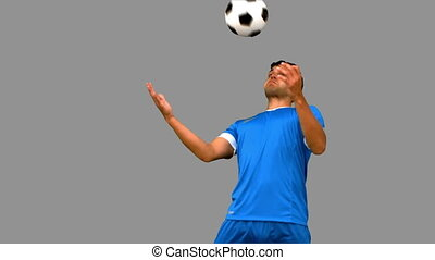Man controlling a football with his chest on grey screen in...