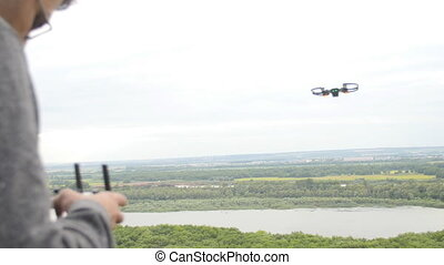 Man controlling a quadrocopter drone above a river