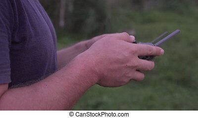 Man controlling drone outdoors. Closeup hands of drone...