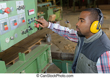 Man controlling industrial machine