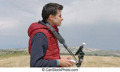 """Man controlling quadrocopter flight, professional cameraman filming aerial video"""