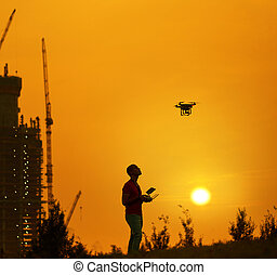 Man controls a quadrocopter at the warm sunset. New building on background