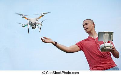 Man controls a quadrocopter in park