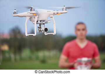 Man controls a quadrocopter. Selective focus on drone, men is blurred