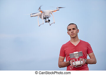 Man controls a quadrocopter. Selective focus on men, drone is blurred