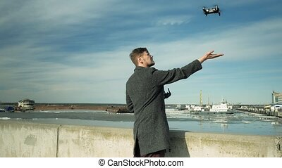 man controls quadcopter outdoors - a man with a beard and...