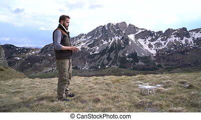 Man controls the drone outdoors in a picturesque place