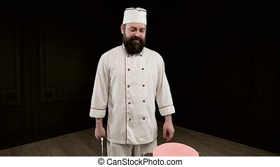 Man cook on black background, holds big knife, aim a blow over cake. Closeup
