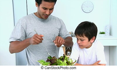 Man cooking a salad with her son in the kitchen