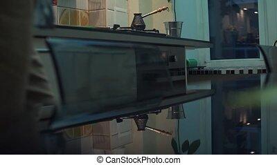 Man cooking coffee in turkish jezve pot at kitchen