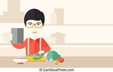 Man cooking food. - An asian man holding a digital tablet...