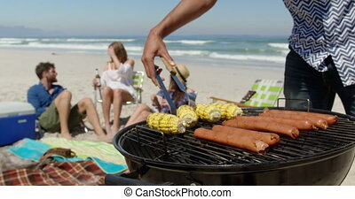 Mid section of African-American man cooking food on barbecue at beach on a sunny day 4k