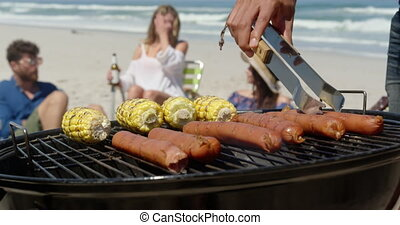 Close-up of African-american man cooking food on barbecue at beach on a sunny day 4k