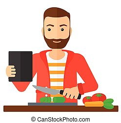 Man cooking meal. - A man holding a digital tablet and...