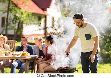 man cooking meat on barbecue grill at summer party -...