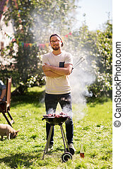man cooking meat on barbecue grill at summer party