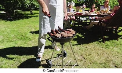 man cooking meat on barbecue grill at summer party - food,...
