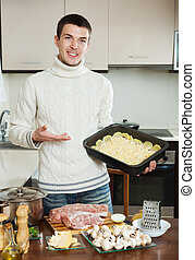 Man cooking meat with mushrooms and potatoes