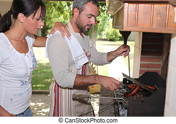 man cooking on barbecue