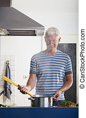 man cooking pasta in a kitchen