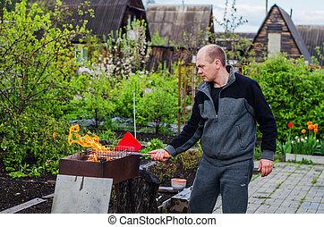 man cooks barbecue