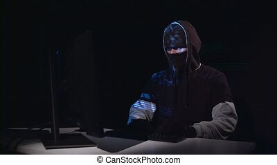 Man copies information from the computer, on the table is a gun. Black background