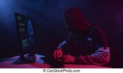 Man copies information from the computer, on the table is a gun. Black smoke background