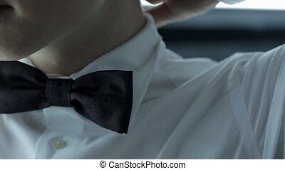 Man correct his dark bow-tie on white jacket indoor.