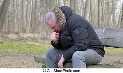 Man coughing on bench in the park